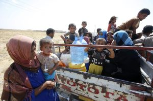 Displaced people from the minority Yazidi sect, who fled from the violence in the Iraqi town of Gwer, wait to return at a check point at the entrance of Gwer